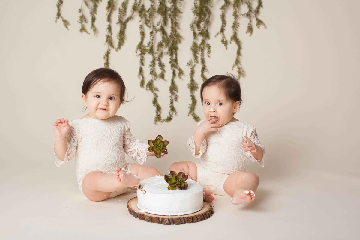 twin  girl cake smash with succulents and cream outfits and greenery