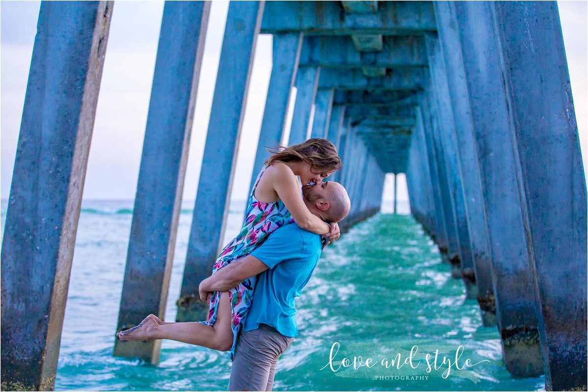 Engagement Photography on Venice Dog Beach under the pier and couple kissing