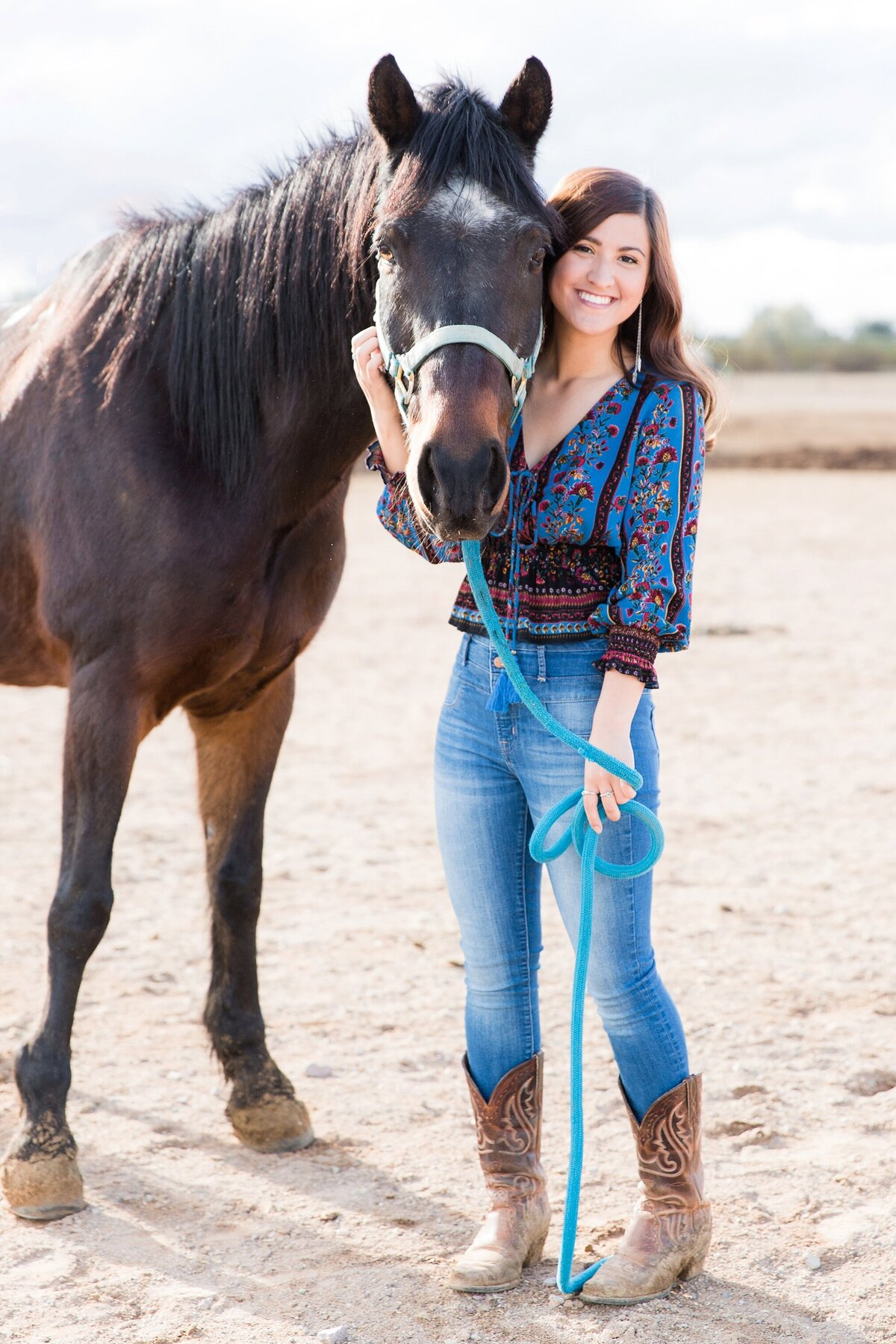 full length portrait of a girl standing next to her horse