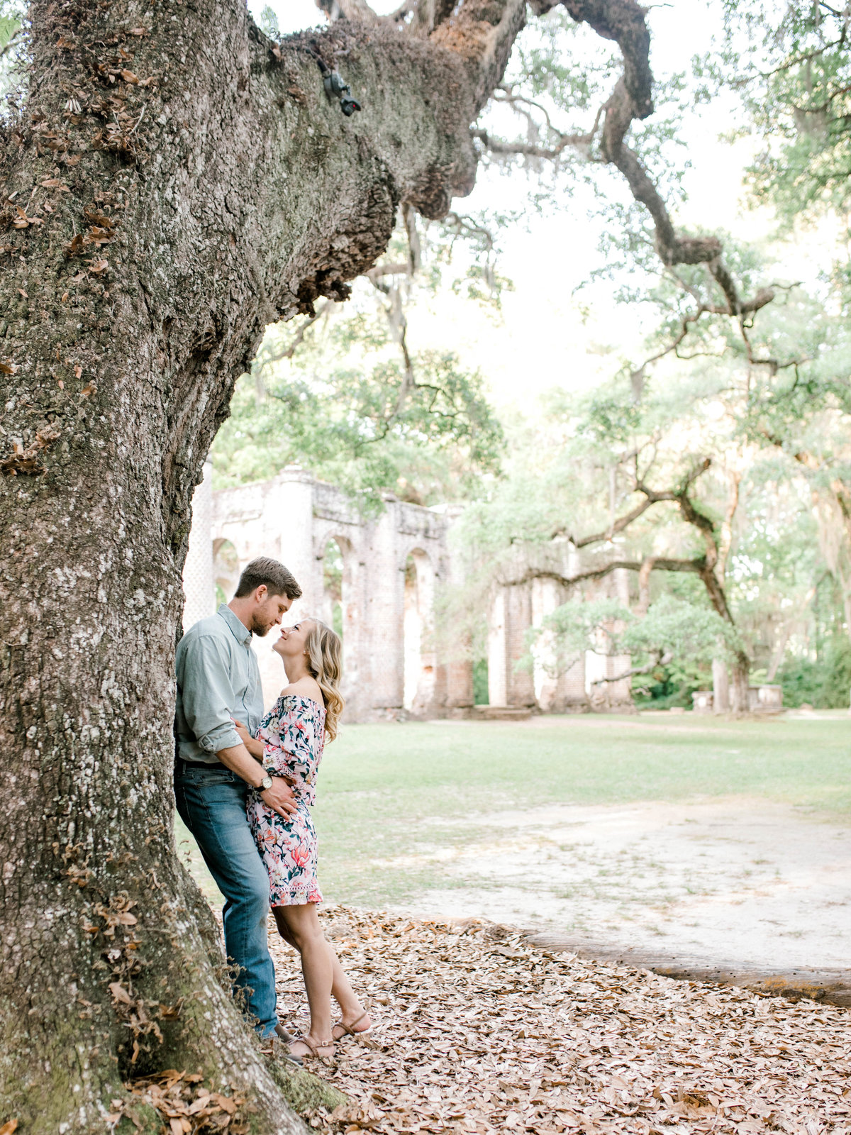 Couple leans on tree with church in background