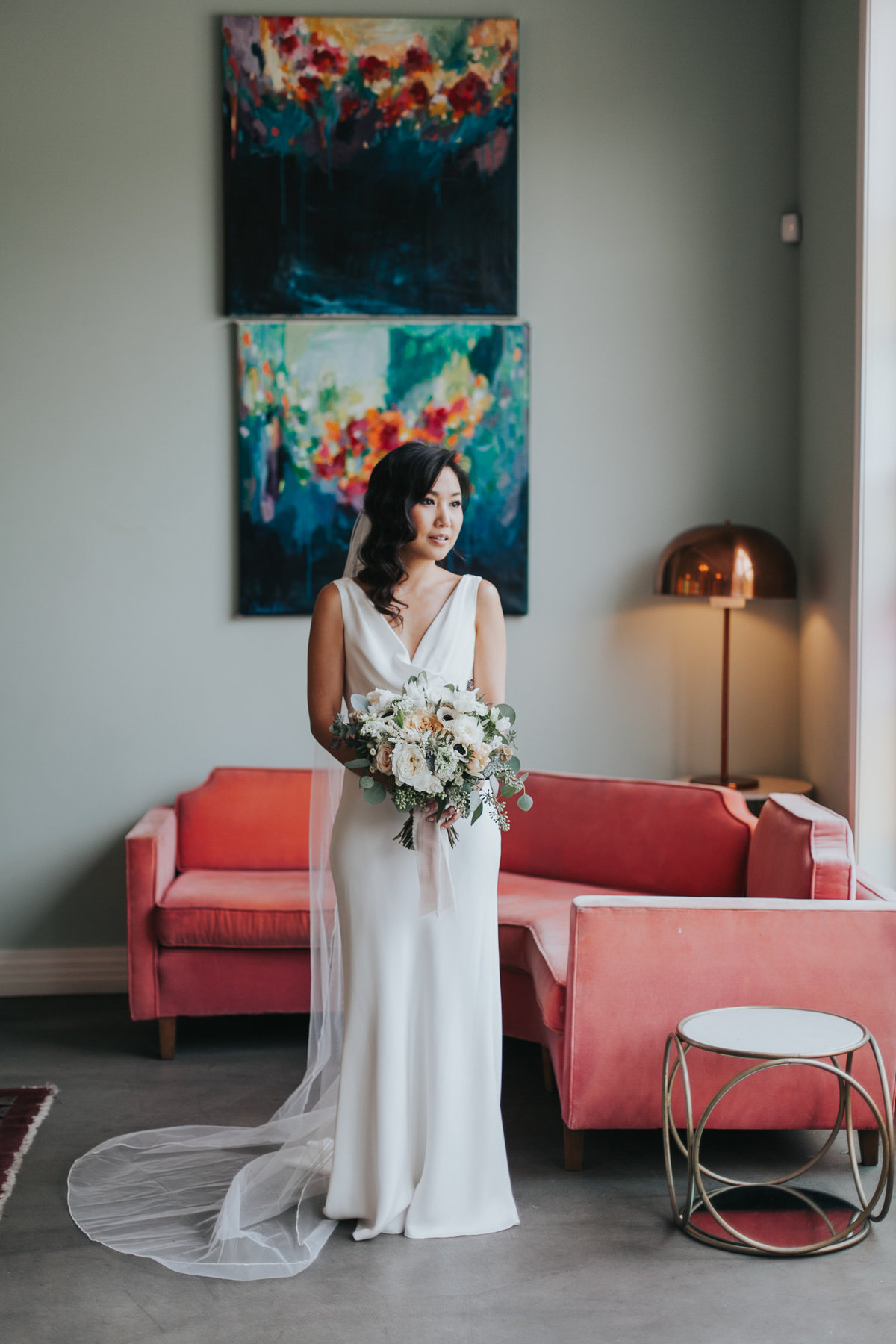 Modern bride wearing simple classic wedding dress and long chapel veil with a white floral bridal bouquet at the  Fig House  wedding in Los Angeles
