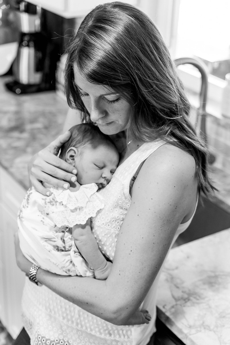 black and white image of mom cuddling newborn daughter in kitchen