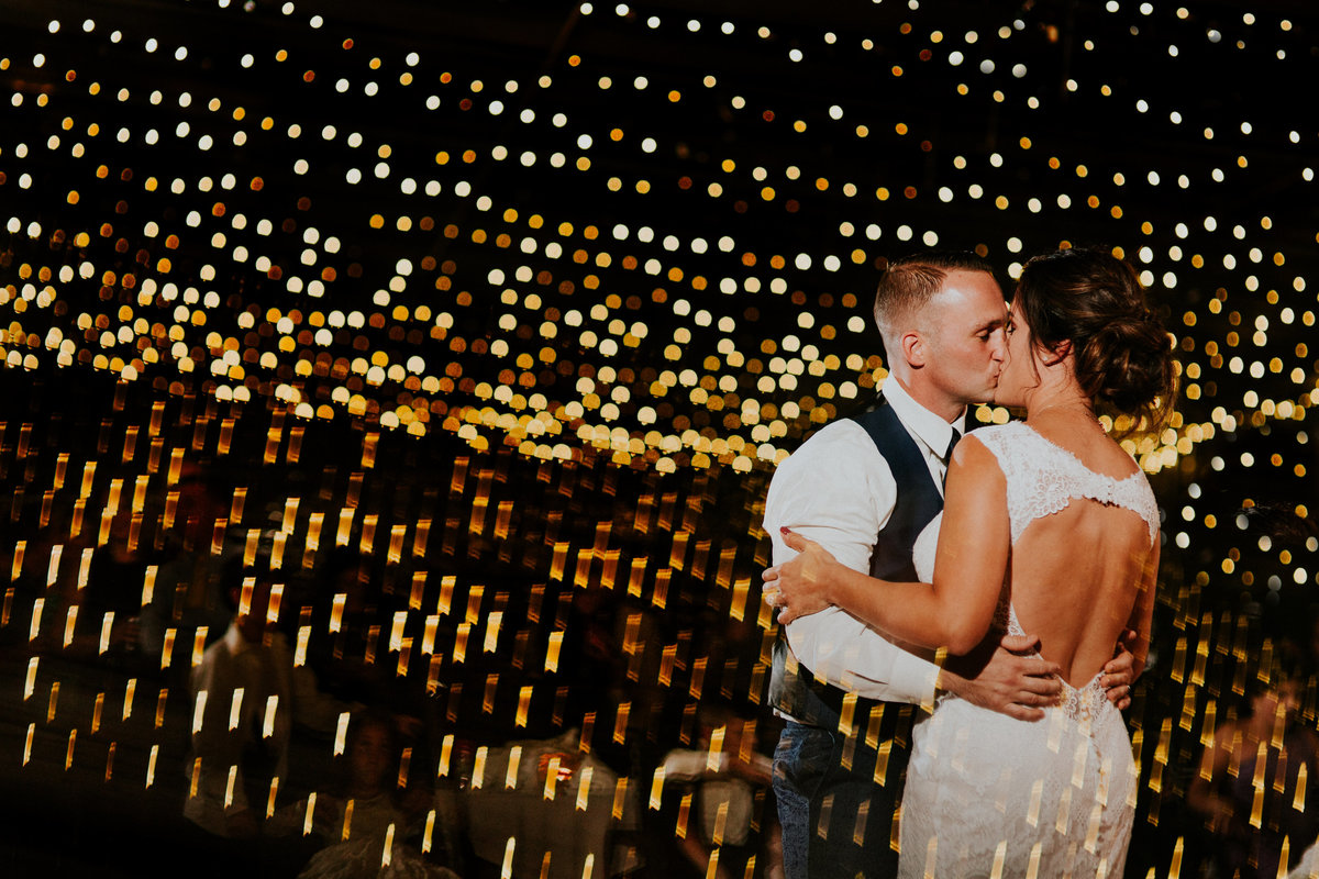 A bride and Groom share a kiss during their first dance under the lights of the Armory