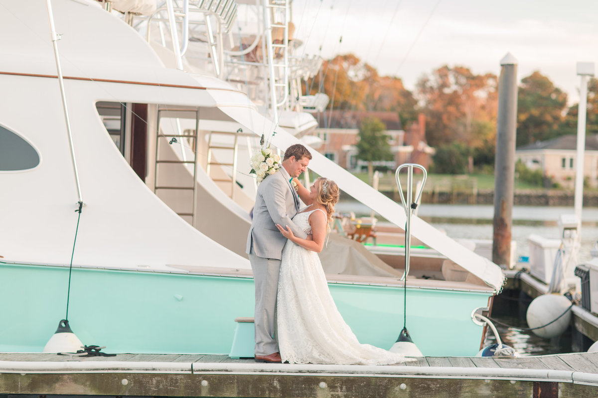 Bride and Groom posing in front of a sea foam green yacht at The Water Table