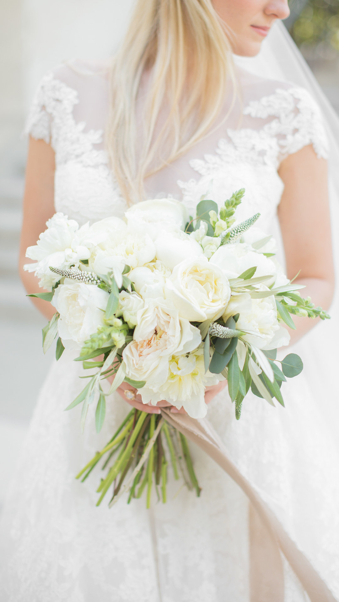 A bride with a soft color palette holds her bridal bouquet