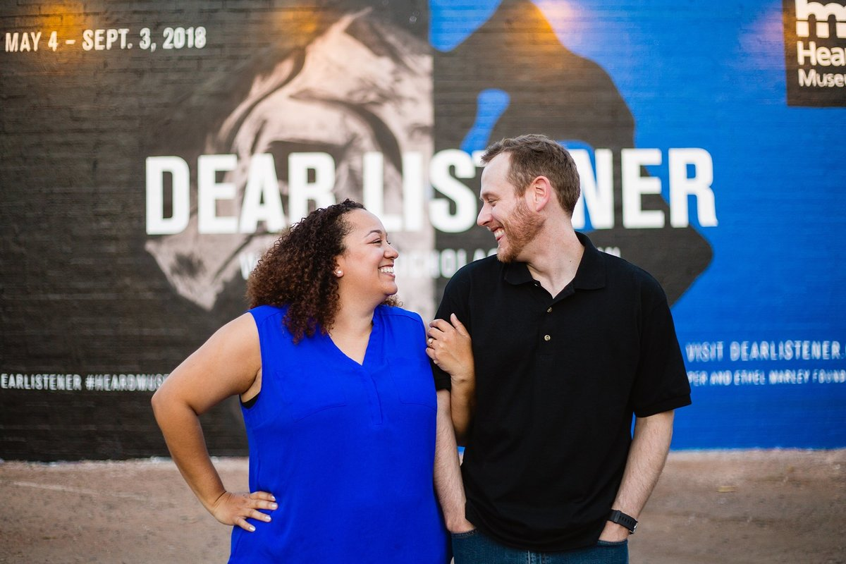 Couple laughing together in front of an art mural during their Roosevelt Row engagement session by PMA Photography.