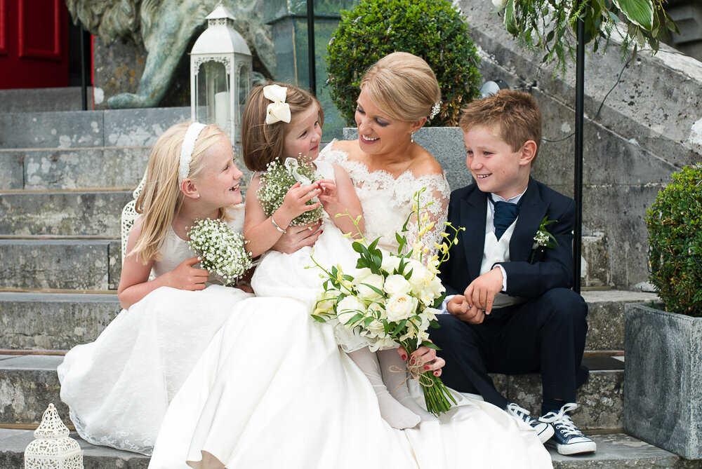 blonde bride wearing a scalloped lace, trumpet style wedding dress and white bouquet, sitting with her flower girls and page boy wearing black Converse trainers
