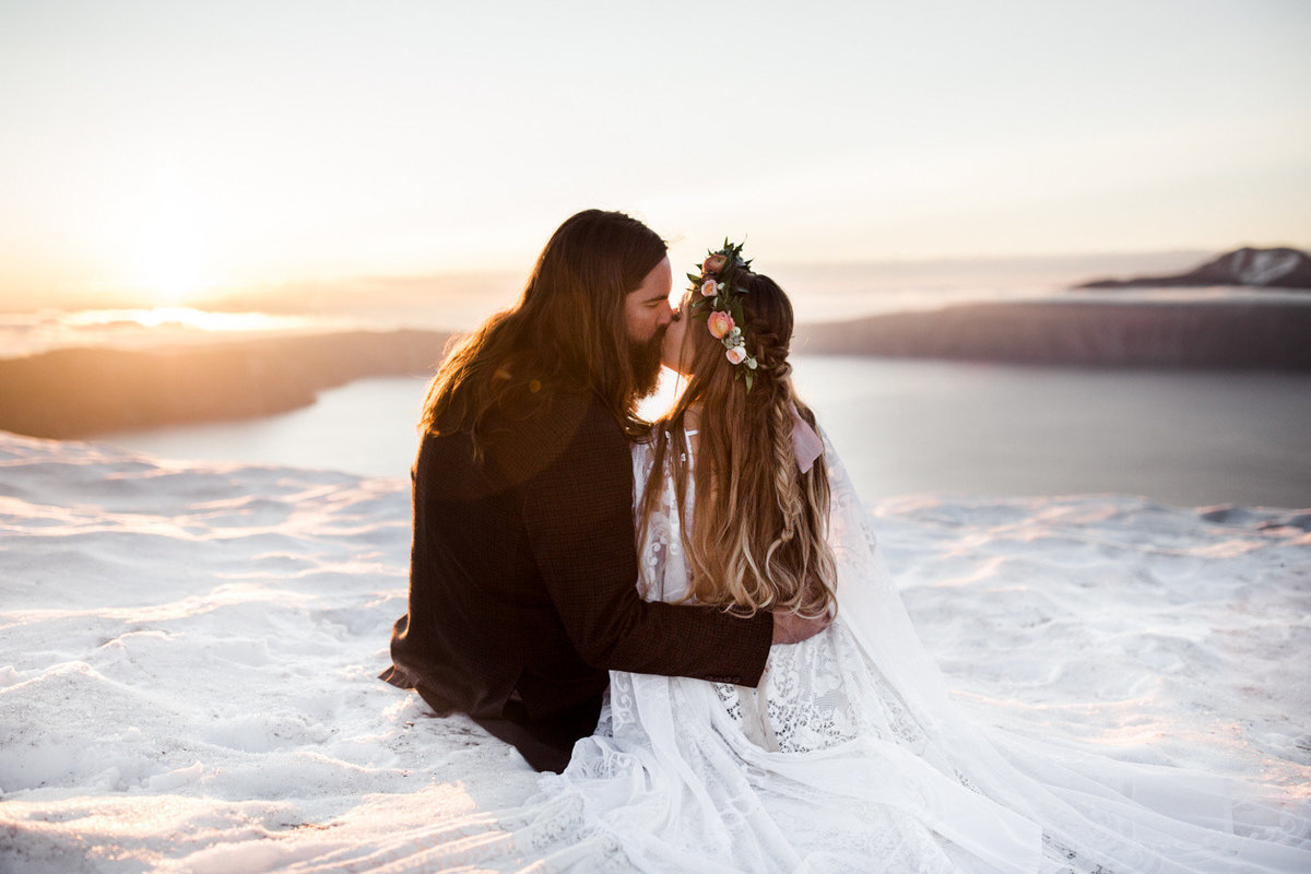 Couple in wedding attire sitting in the snow  and kissing a top an overlook.
