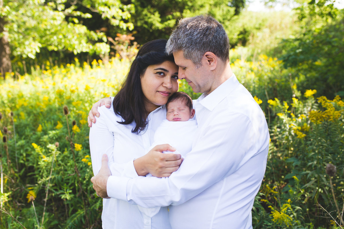 Parents hugging with newborn baby boy in between them outdoors  {Mississauga Family Photographer}