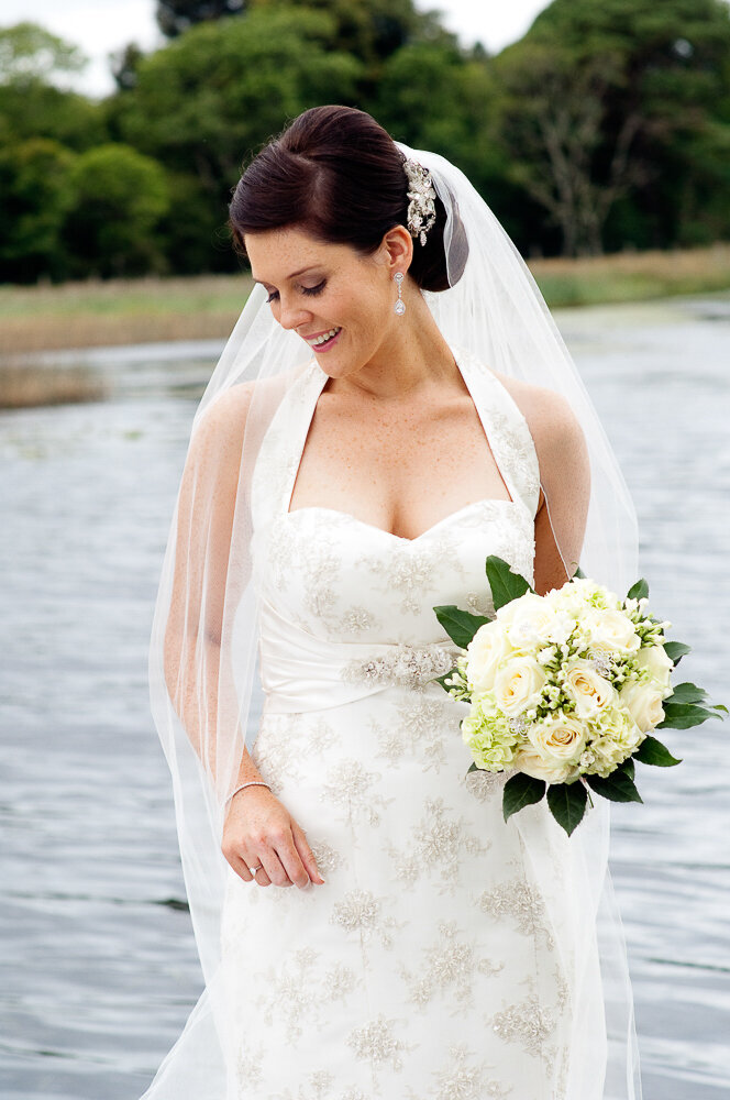 brunette bride wearing a lace, halter neck wedding dress with diamante hairpiece and veil, holding a white flower bouquet beside a lake in Killarney