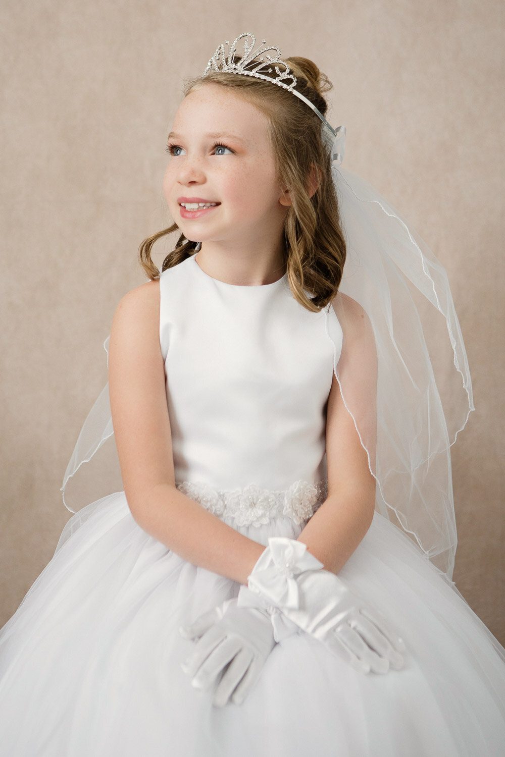 Professional little beauty portrait of girl in white dress and tiara