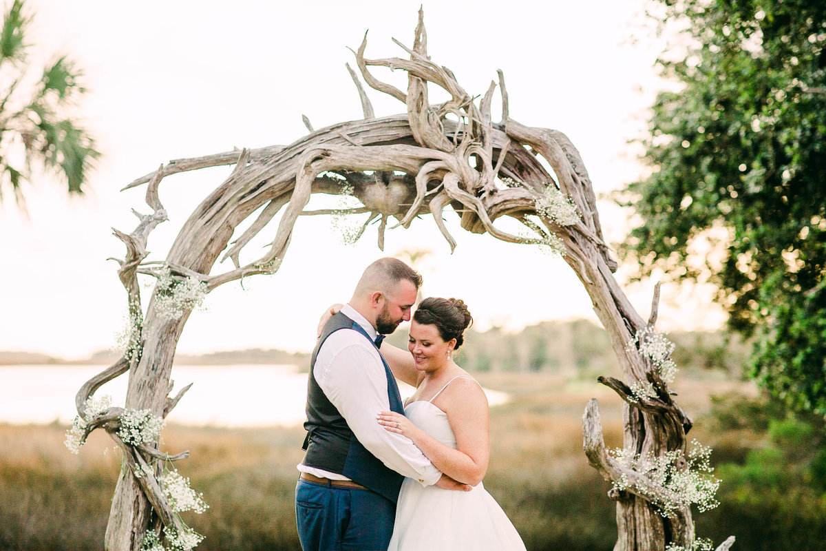 Bride and groom underneath driftwood arbor at La Casa on Mason Creek