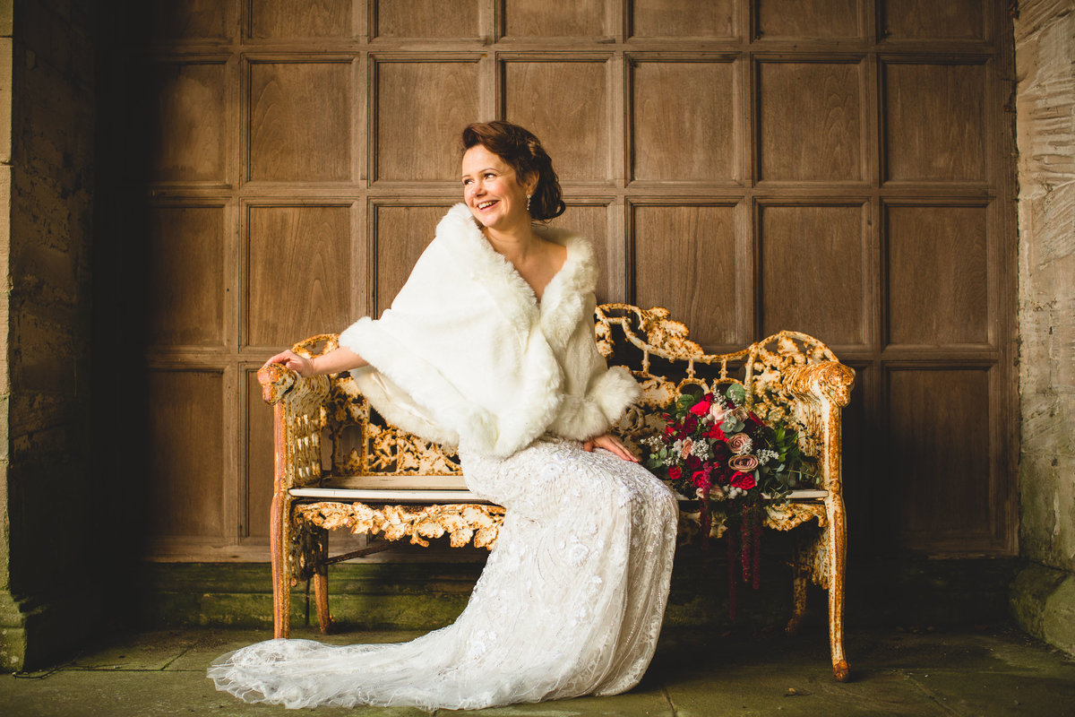 a bride in a vintage wedding lace dress with fur shrug sat on a bench at thornton manor