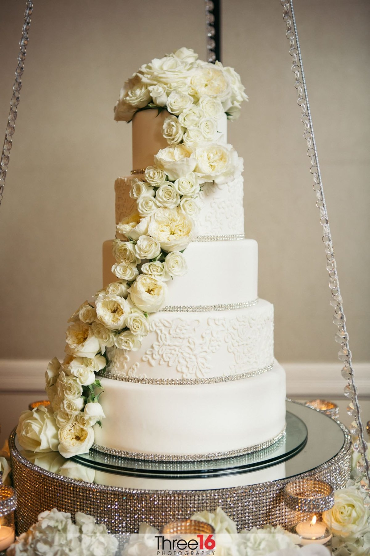 White 5-tiered wedding cake with flowers draped along the side