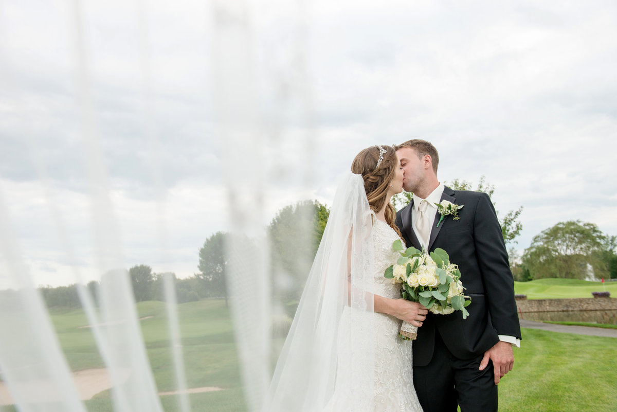 bride and groom kissing photo on the golf course at Willow Creek Golf and Country Club wedding photo