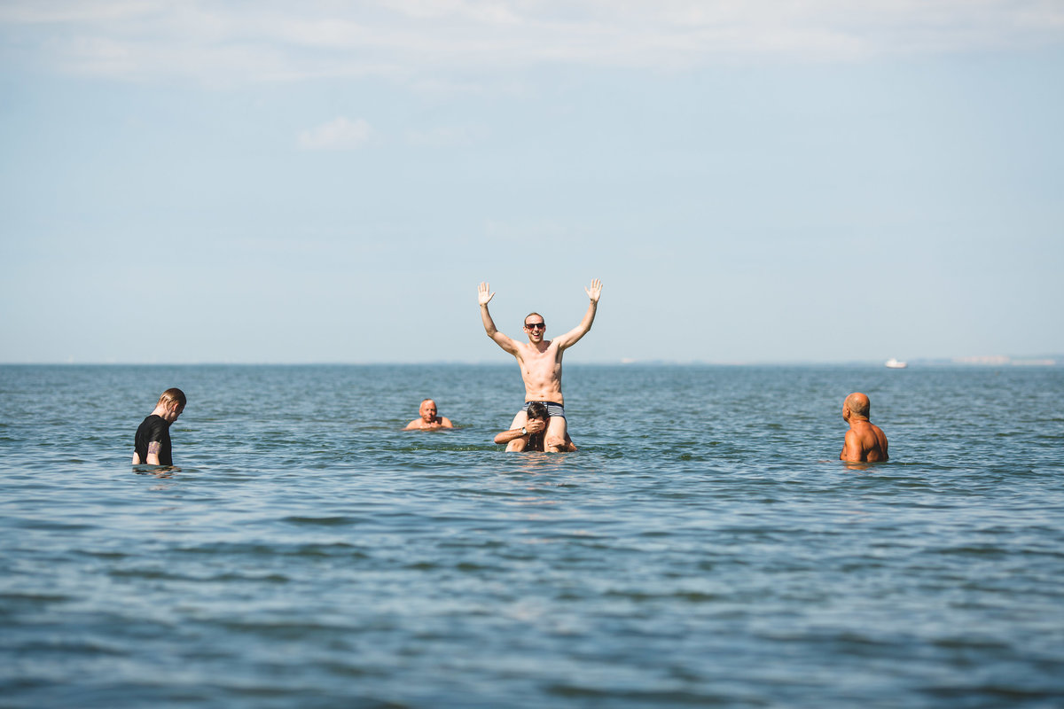 groomsmen swimming in the sea before the wedding