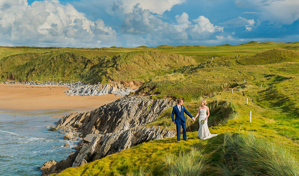 Bride in A-line wedding dress holding hands with red haired groom wearing a navy suit, standing on cliffs overlooking the beach in Kerry
