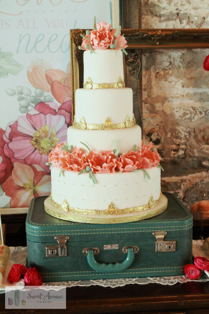 four tier ivory wedding cake with peach flowers and gold trims