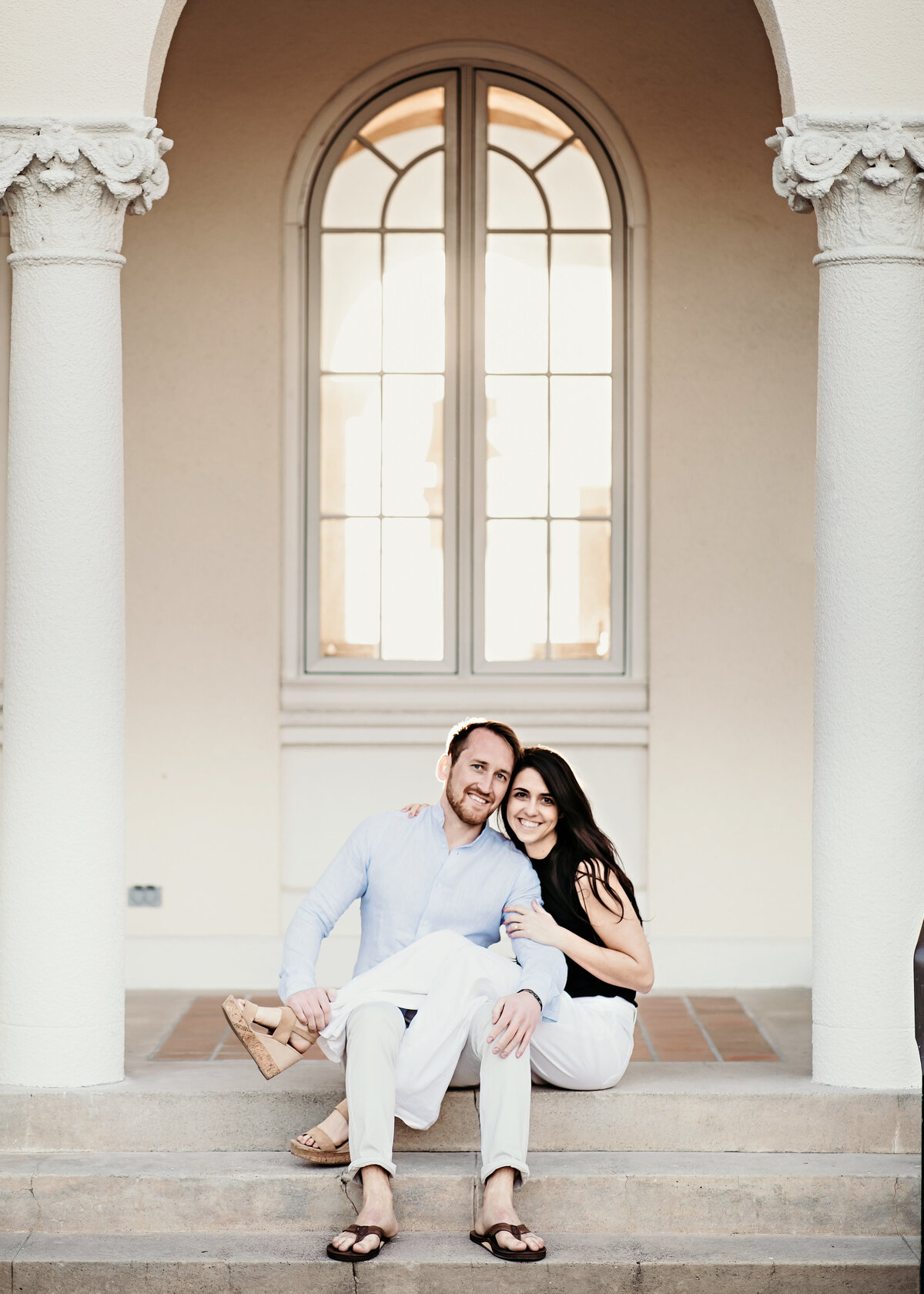 A photograph of an engaged couple sitting next to vintage columns and an arched window, relaxing as the woman drapes her legs across her fiance's lap and they romantically touch faces by Garry & Stacy Photography Co - Orlando Florida engagement photography