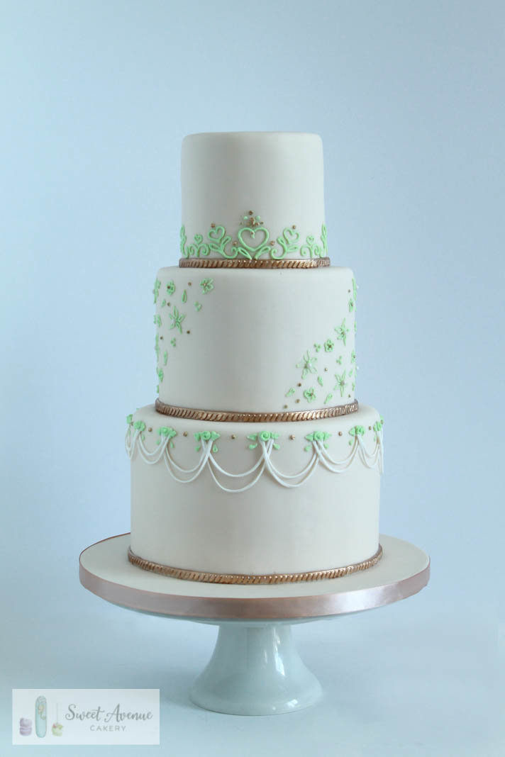 ivory and mint wedding cake with piped lace and gold trims