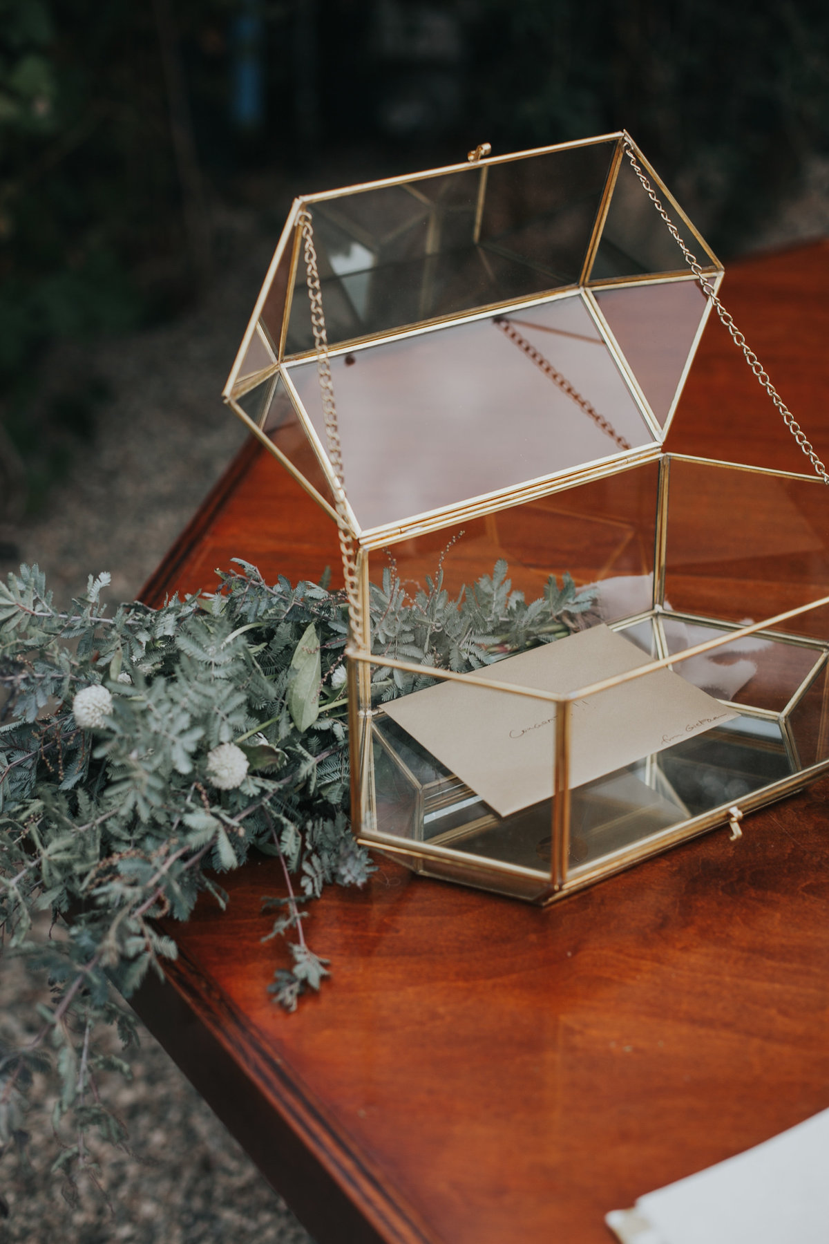 Wedding welcome table with glass geometric cardbox and eucalyptus leaves