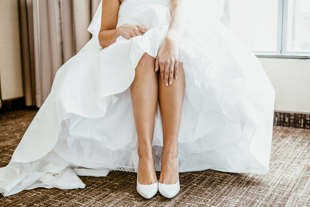 Bride sitting on a chair in her wedding dress and showing her engagement ring