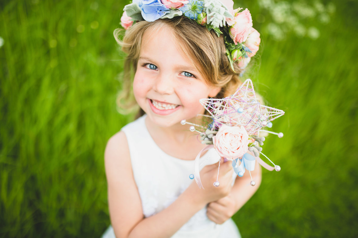a flower girl with floral crown and wand
