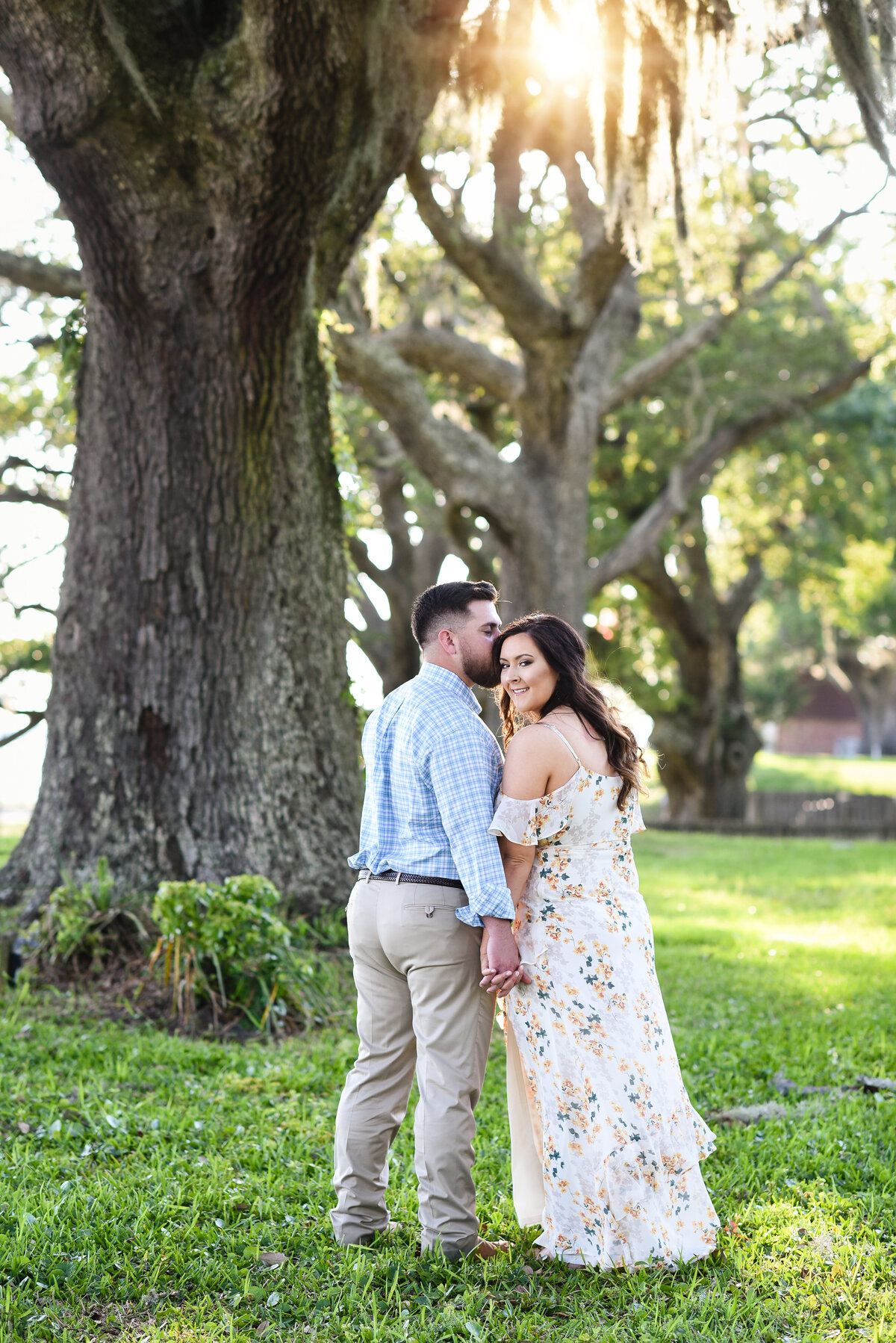 Beautiful Mississippi Engagement Photography: Couple walks away under Spanish moss as the sun sets in Ocean Springs, MS