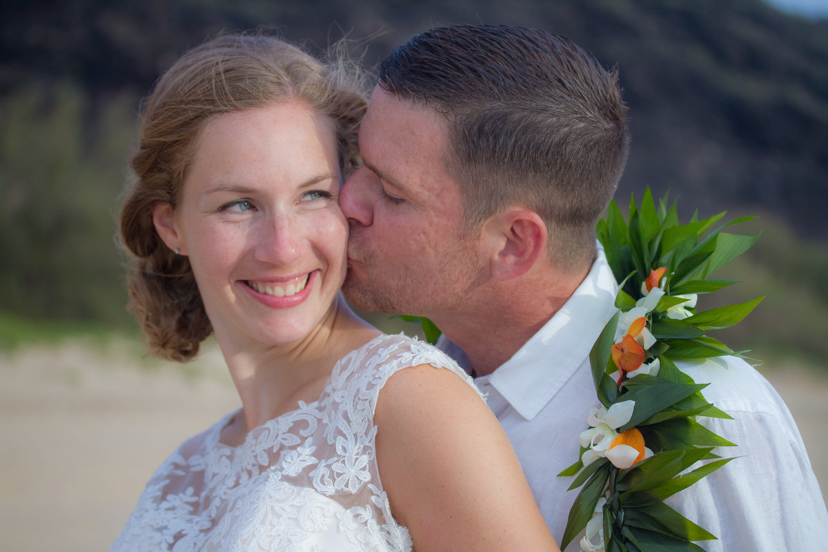 Groom wearing a lei kissing his bride at their beach wedding in Kauai.