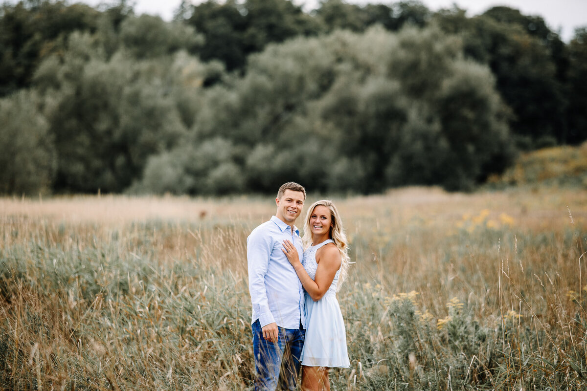 Engaged couple embracing in field in Buffalo, New York