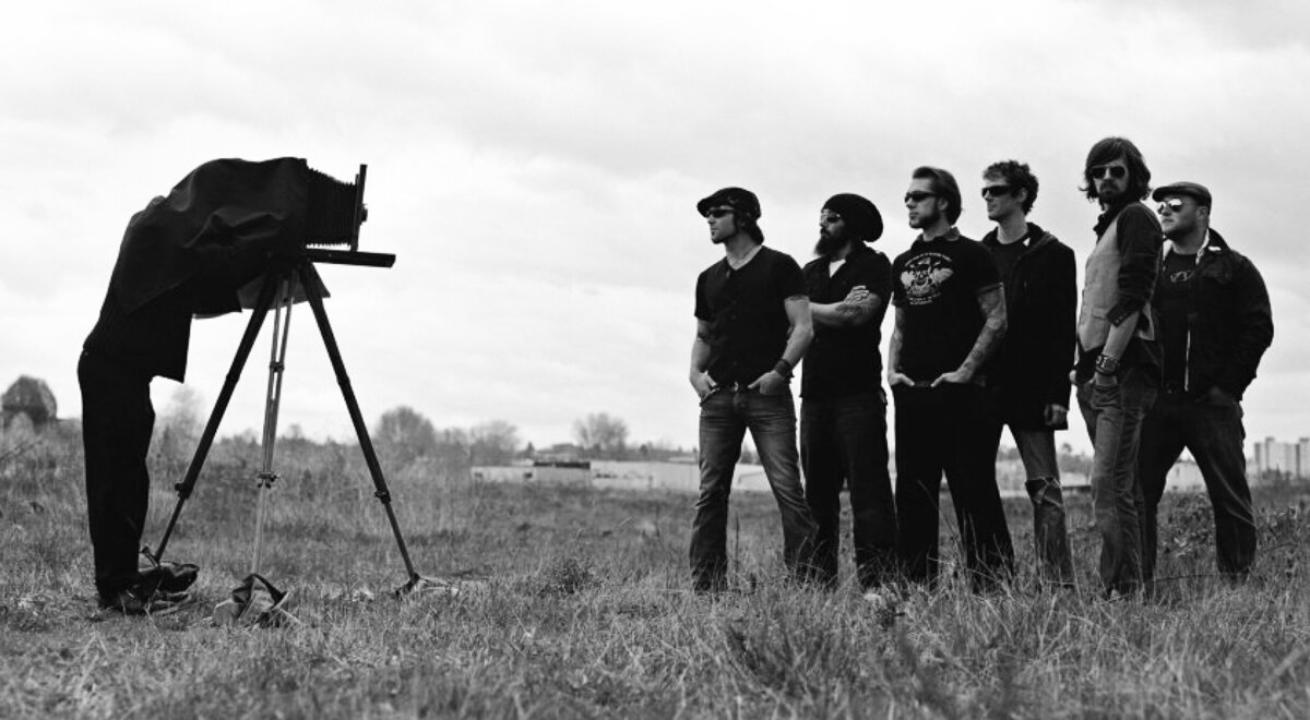 Band portrait seven members of The Matinee standing in field facing old fashioned camera photographer under cloth taking photo black and white image