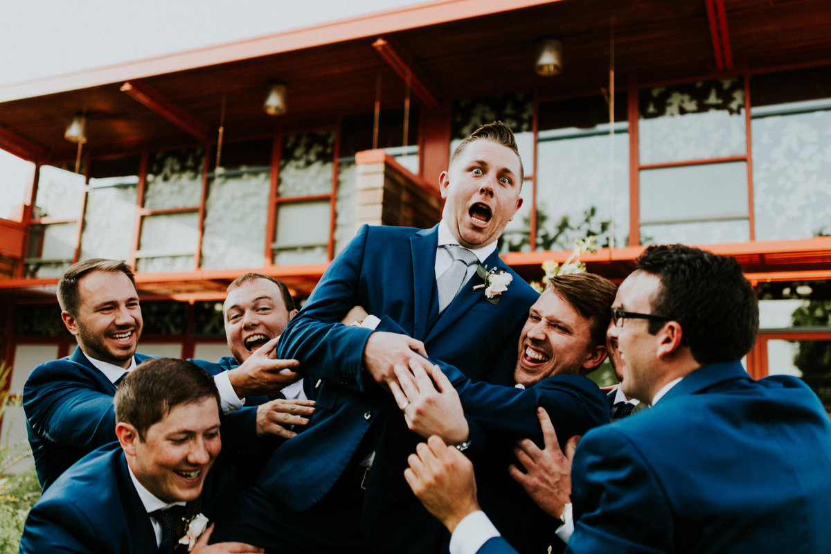 Summer wedding  at the grange insurance audubon center in columbus ohio. The groomsmen lift the groom into the air after the ceremony