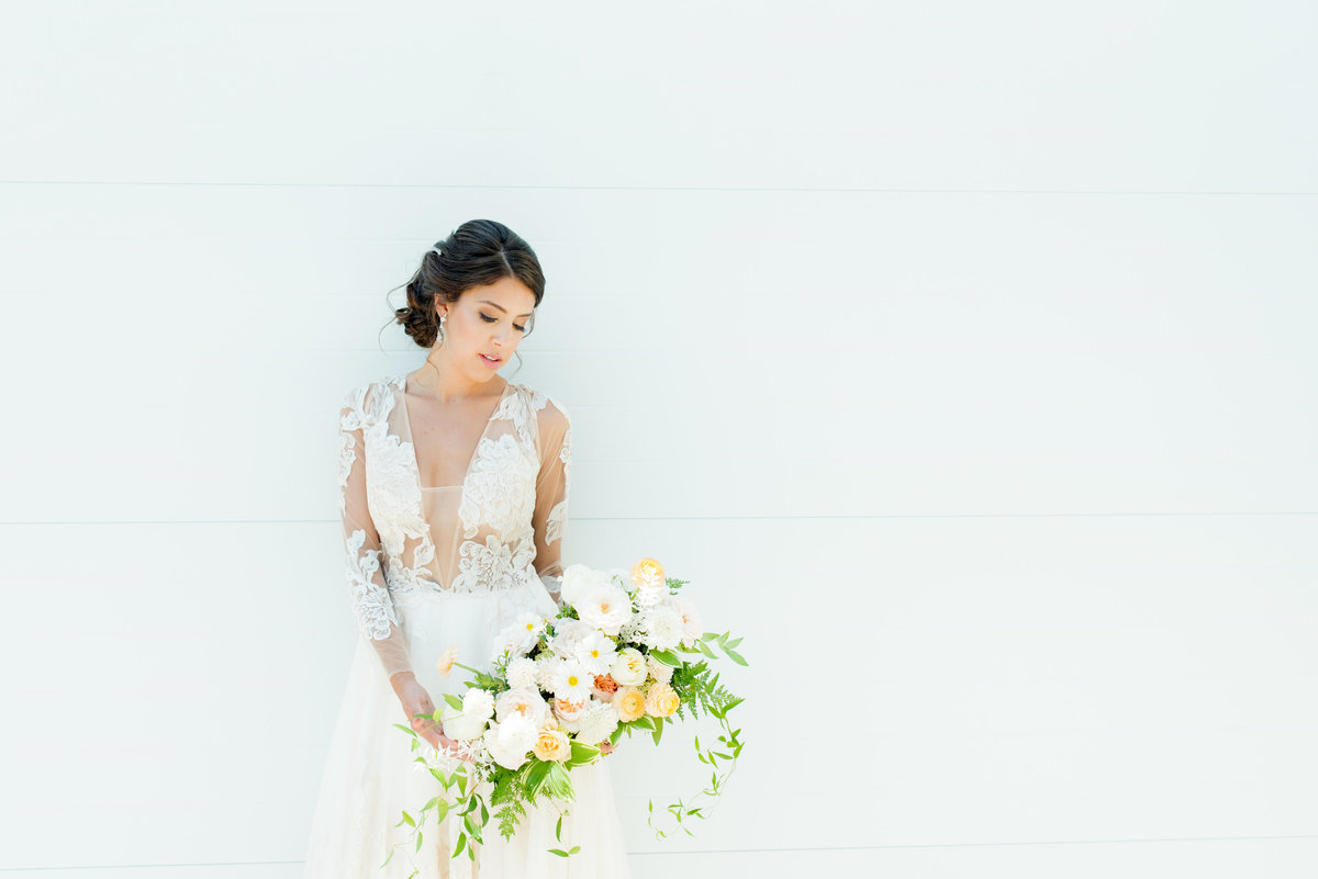 bride holding organic bouquet wearing sheer lace sleeved wedding gown