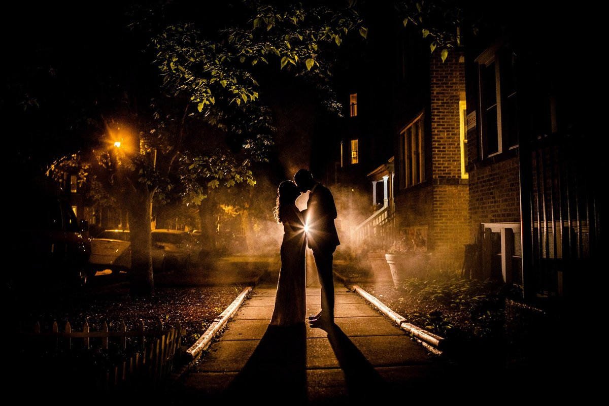 A couple kisses in silhouette at a Firehouse Chicago wedding.