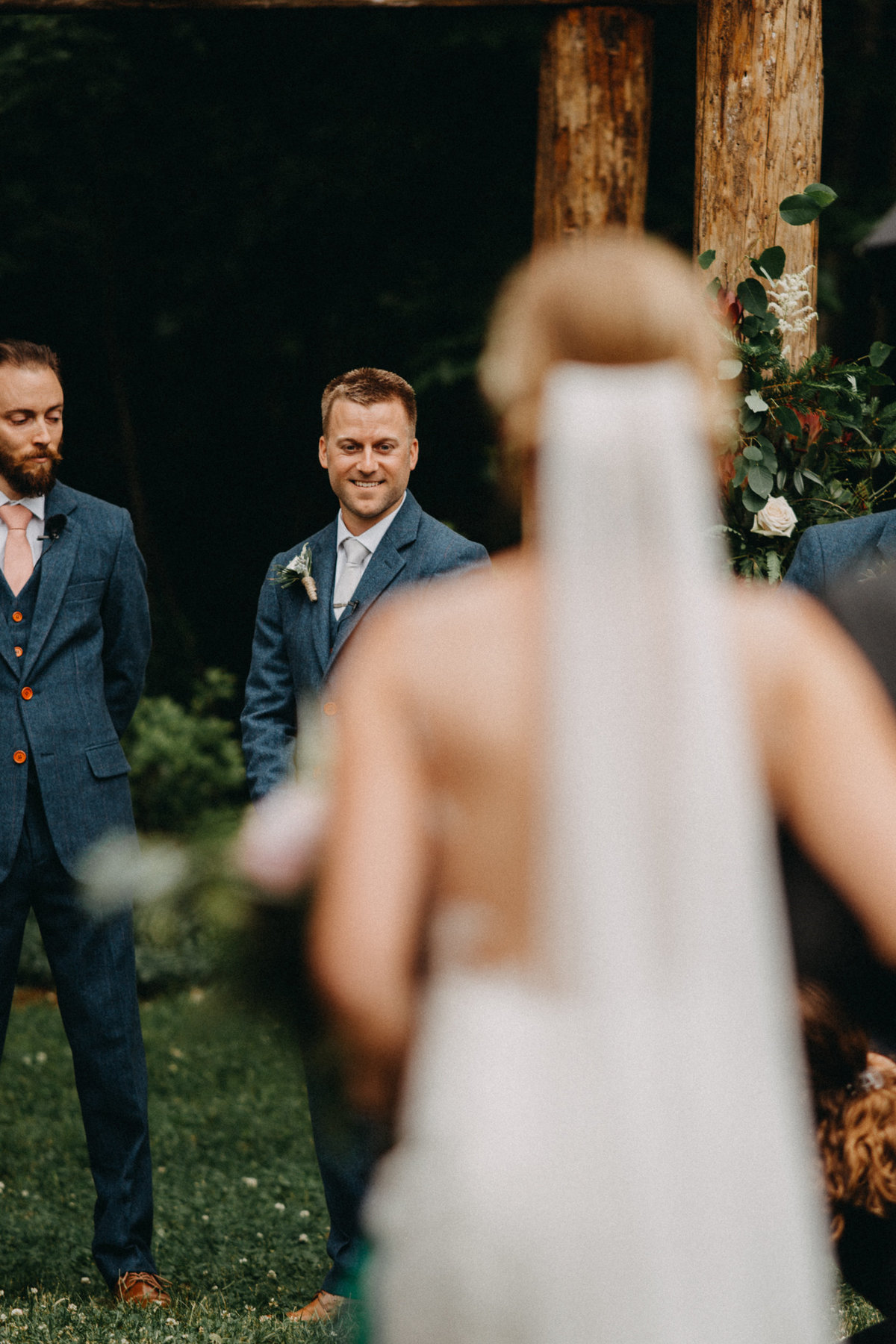 Groom looking at bride walking down aisle