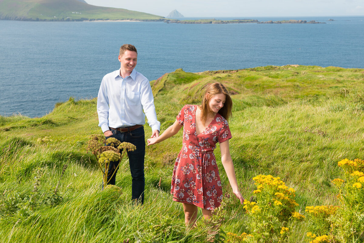 Young couple holding hands and standing in a green field with yellow flowers and overlooking the sea