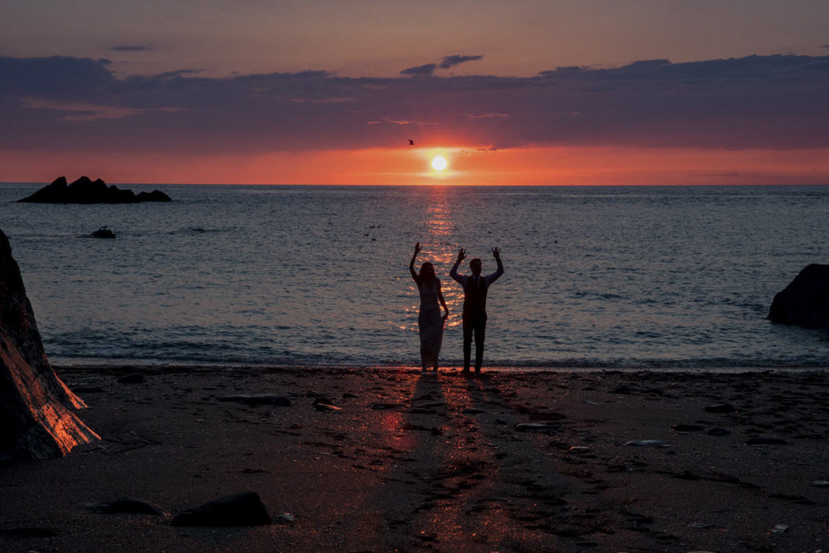Couple waving at sunset Tunnels Beaches Wedding
