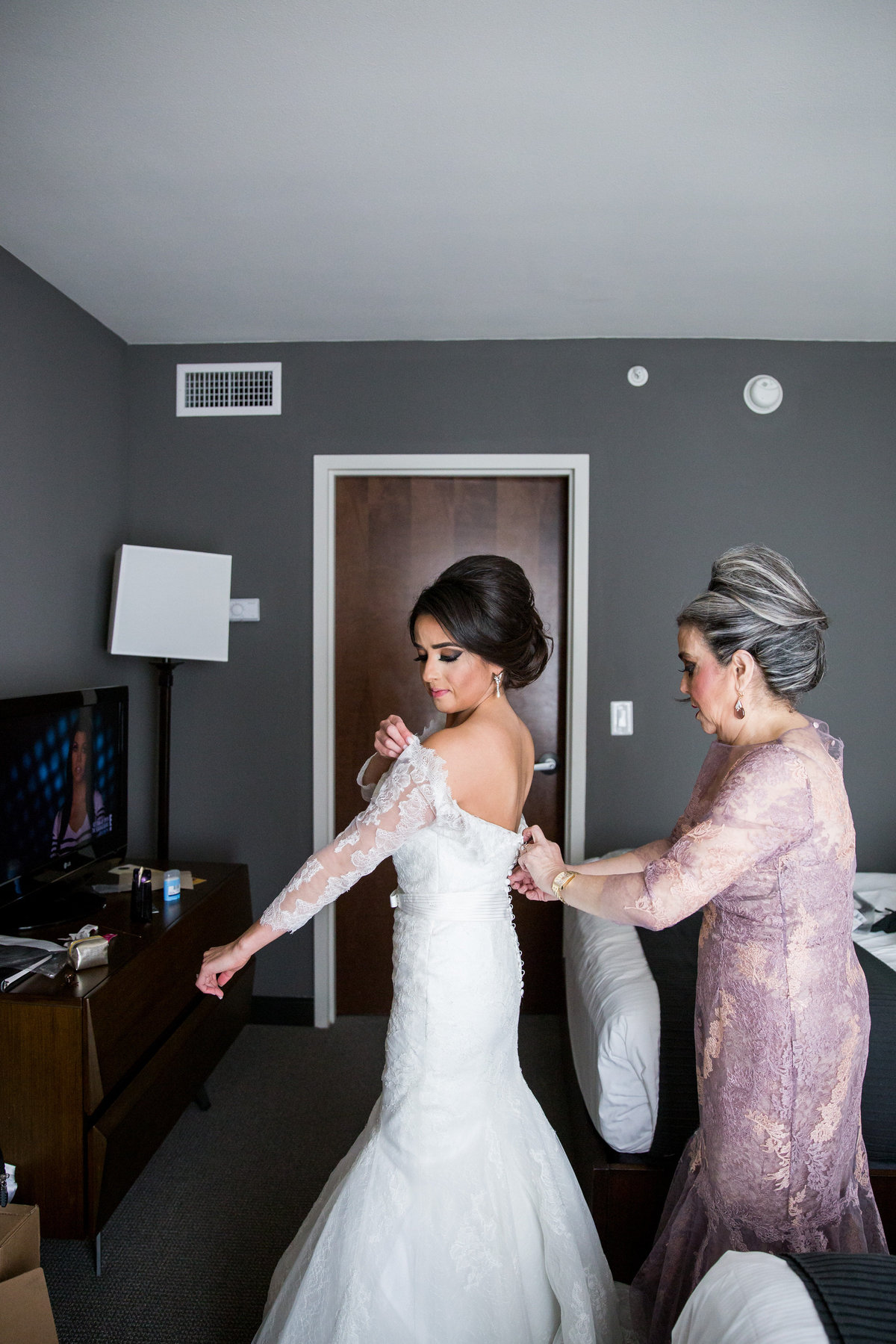 Mother of bride helps her daughter put on wedding gown before wedding ceremony at Contessa Hotel in downtown San Antonio