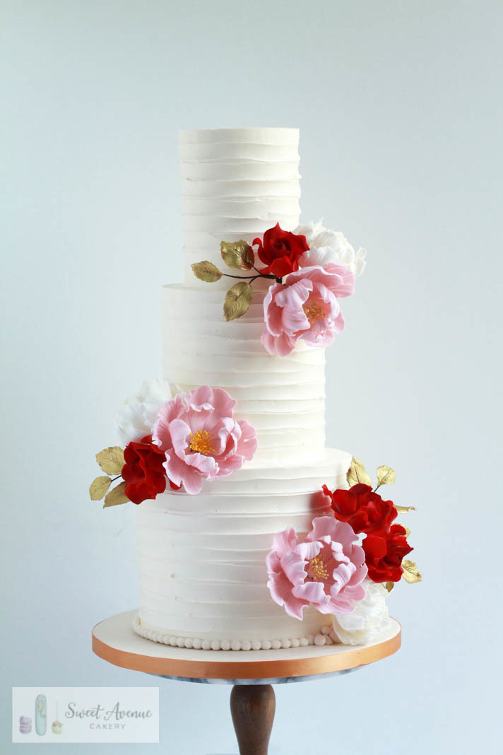 striped buttercream cake with red and blush peonies