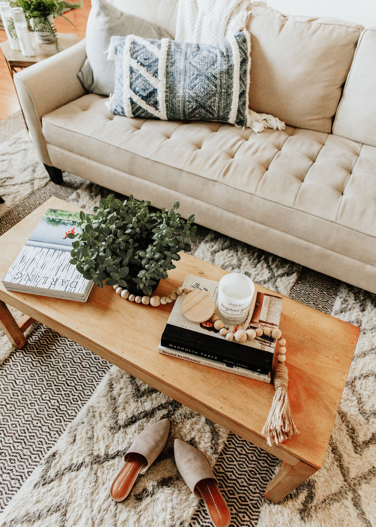 A luxury boho chic lounge is designer with a beige sofa and scandi rug
