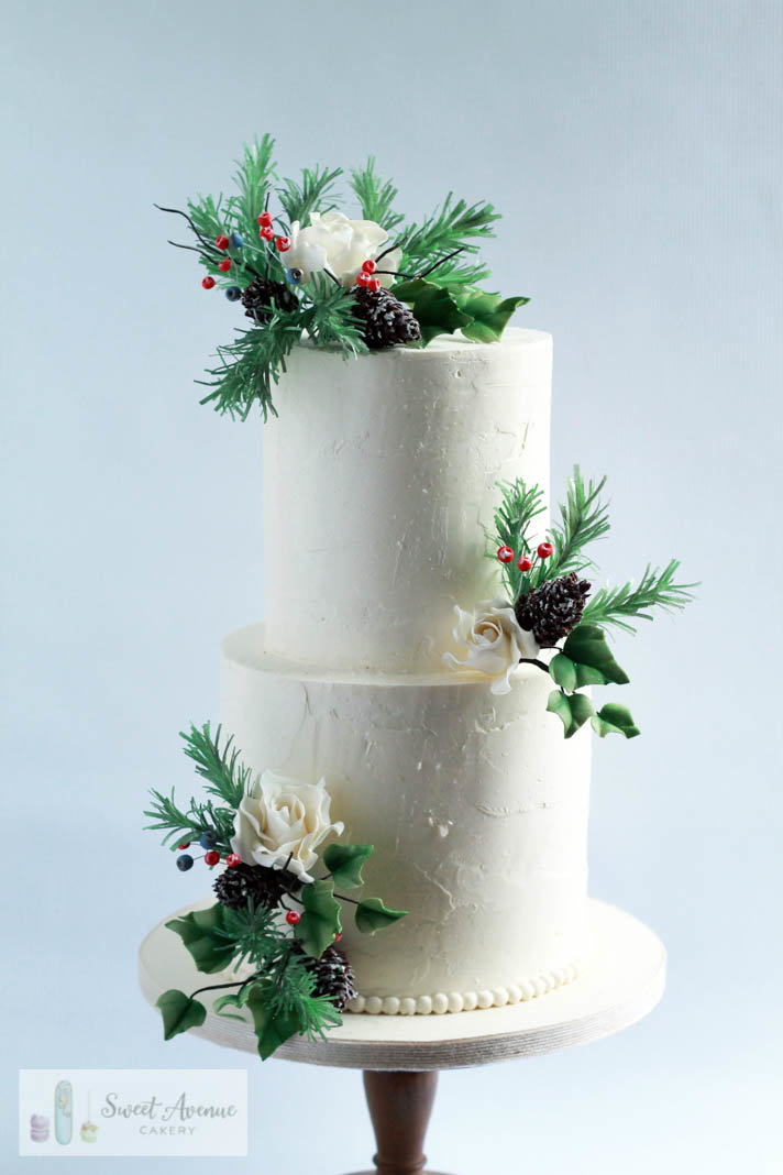 textured buttercream winter wedding cake with evergreens foliage and flowers