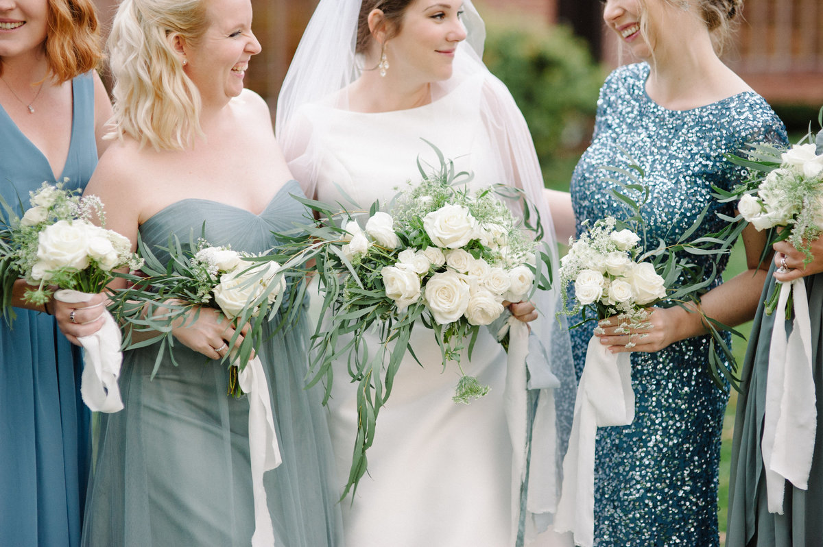 Dusty blue bridesmaids dresses and green and white bouquets