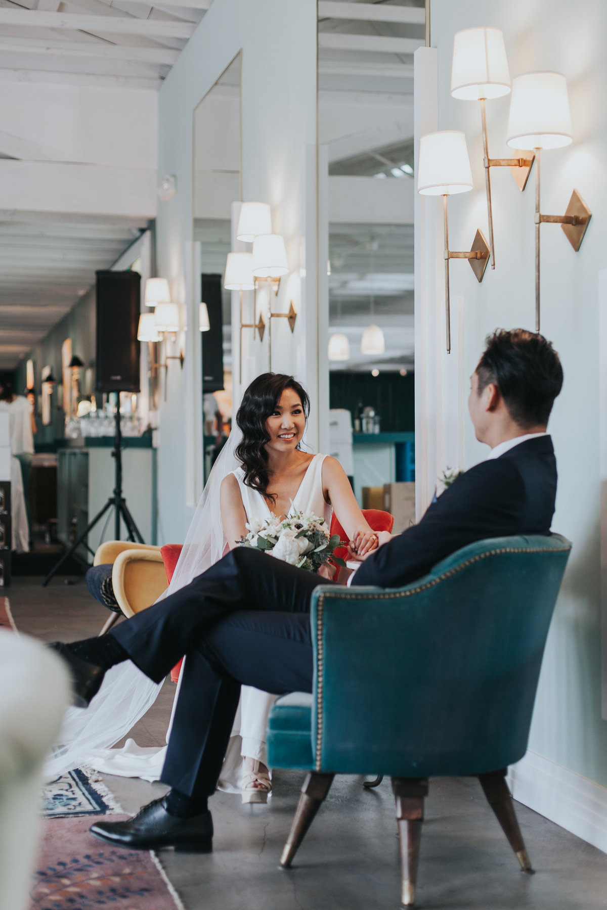 Modern bride and groom sitting in lobby of the Fig House before their wedding