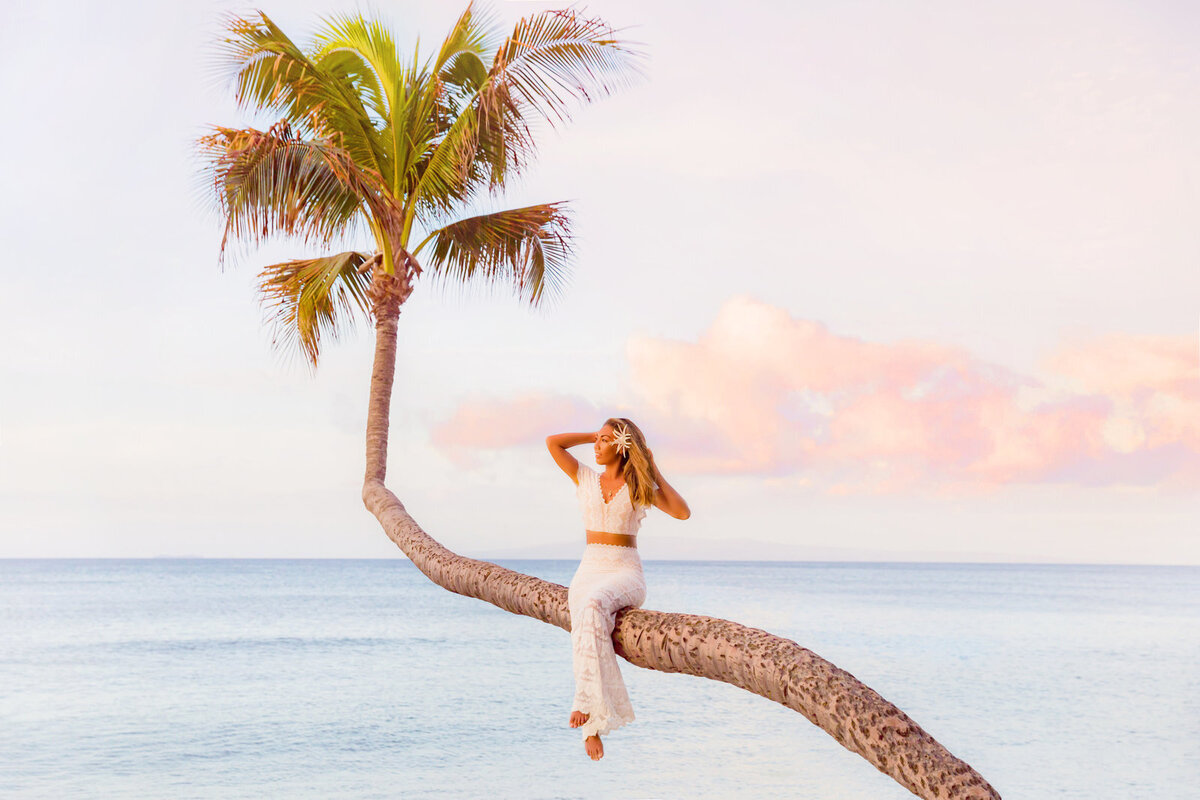 Newlywed Maui bride posing on a palm tree in Hawaii