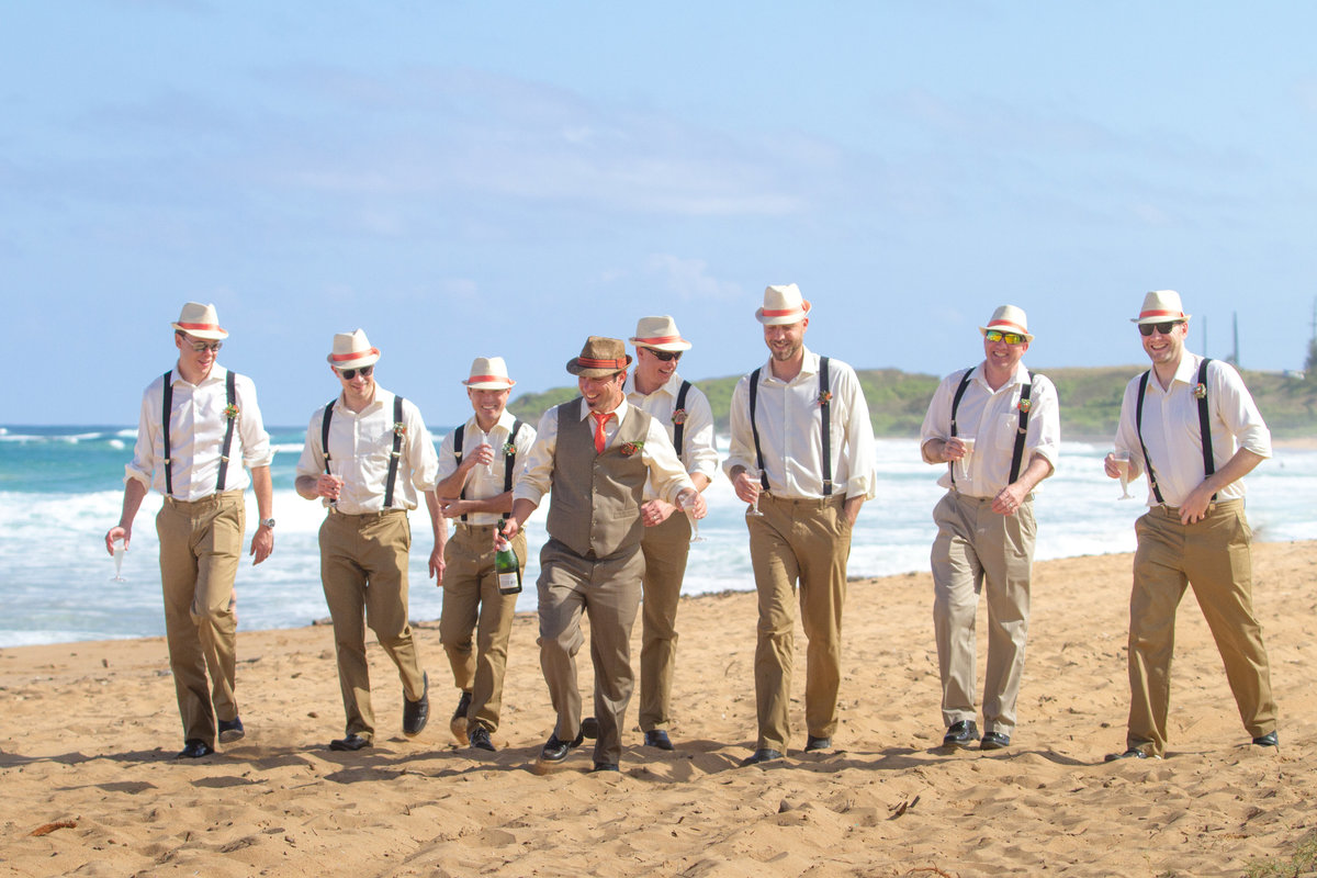 Hipster groomsmen wearing fedoras and suspenders walking the beach in Kauai.