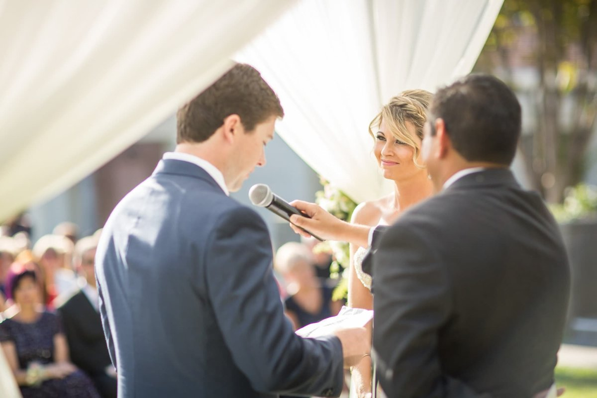 Bride watches her Groom as he reads his vows to her