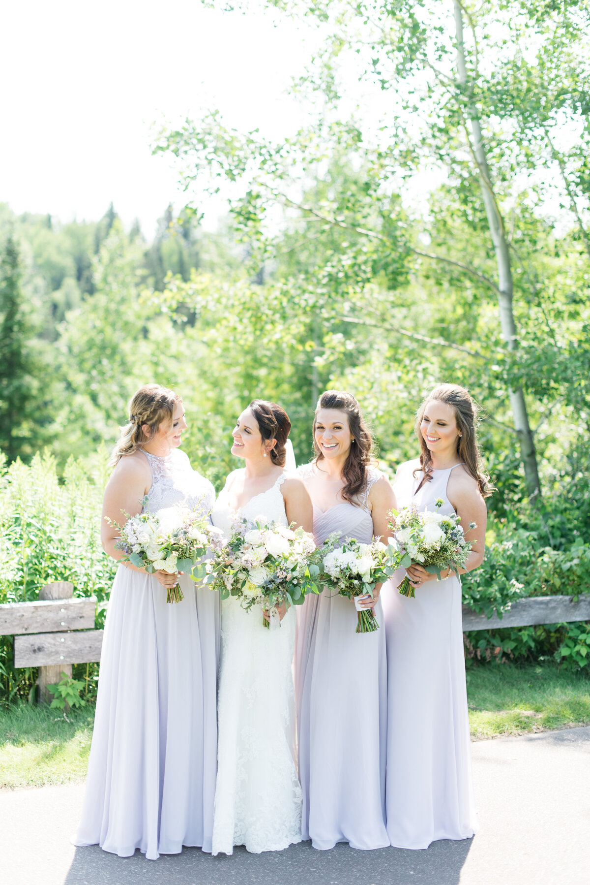 A bride and her bridesmaids giggle during their portraits at Whitewater Golf Club in Thunder Bay