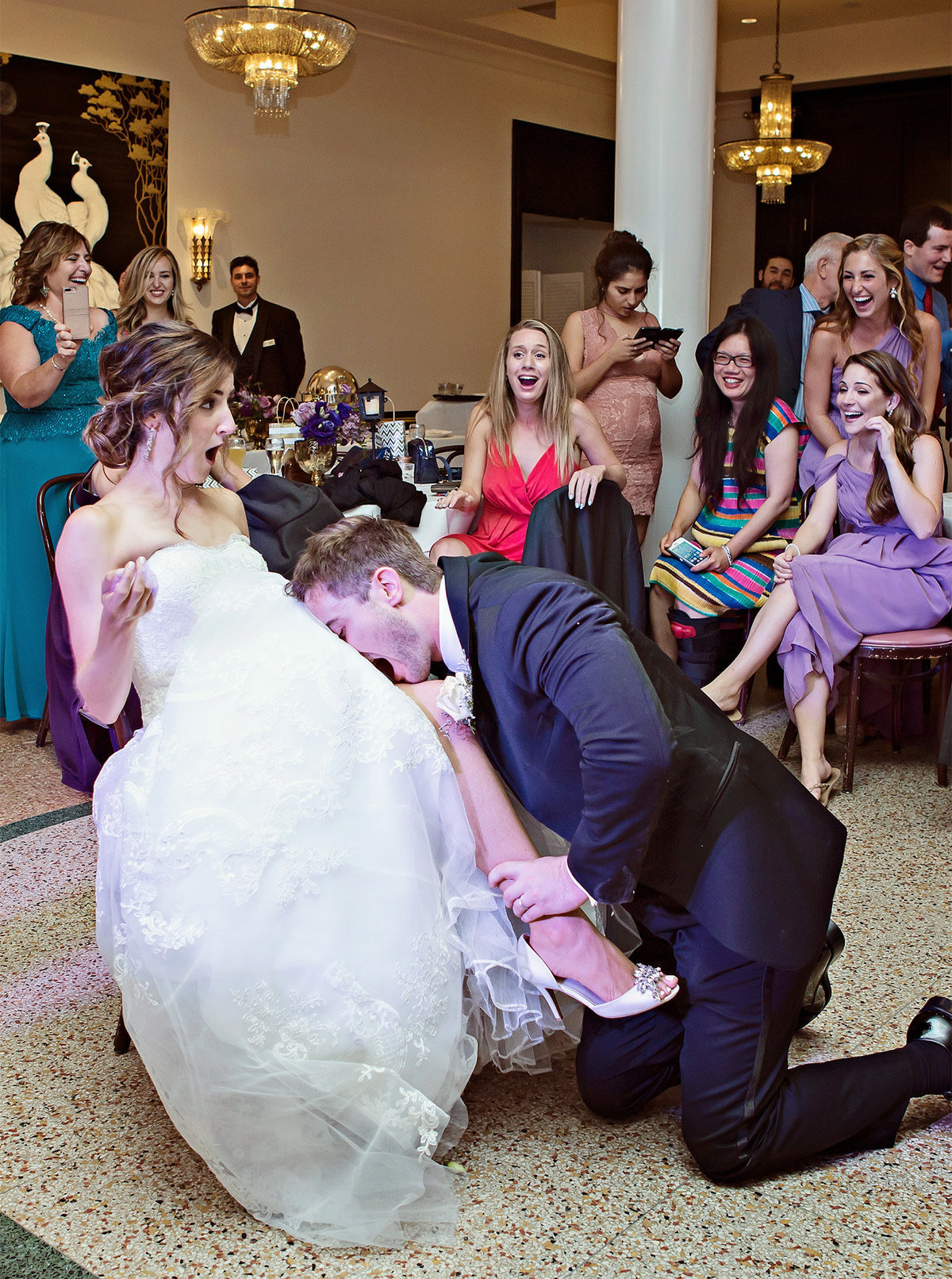 groom takes bride's garter off with his mouth during wedding reception at Arnaud's Restaurant New Orleans