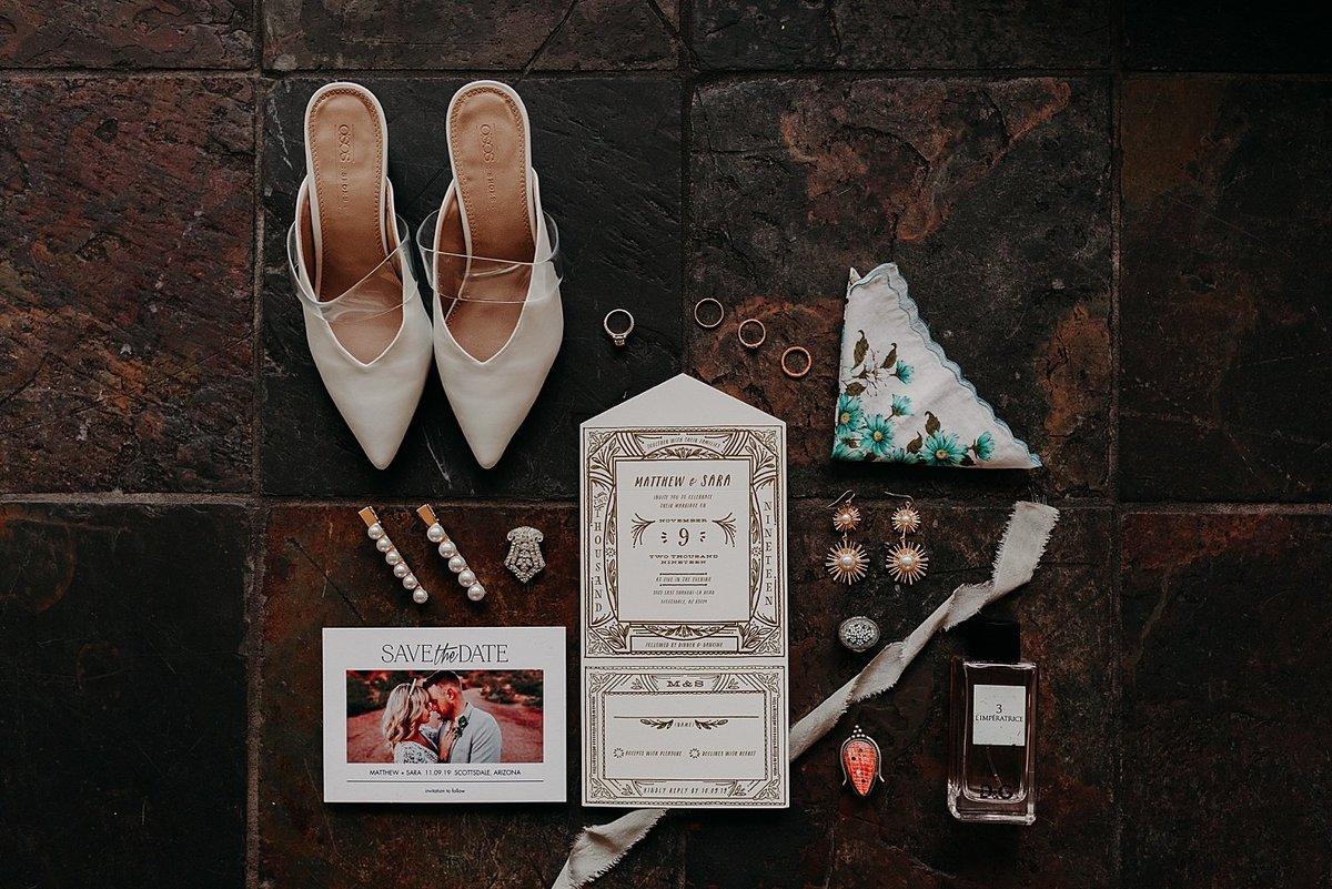 Bride's shoes, invitation suite, vintage jewelry, and handkerchief are styled on tile floor