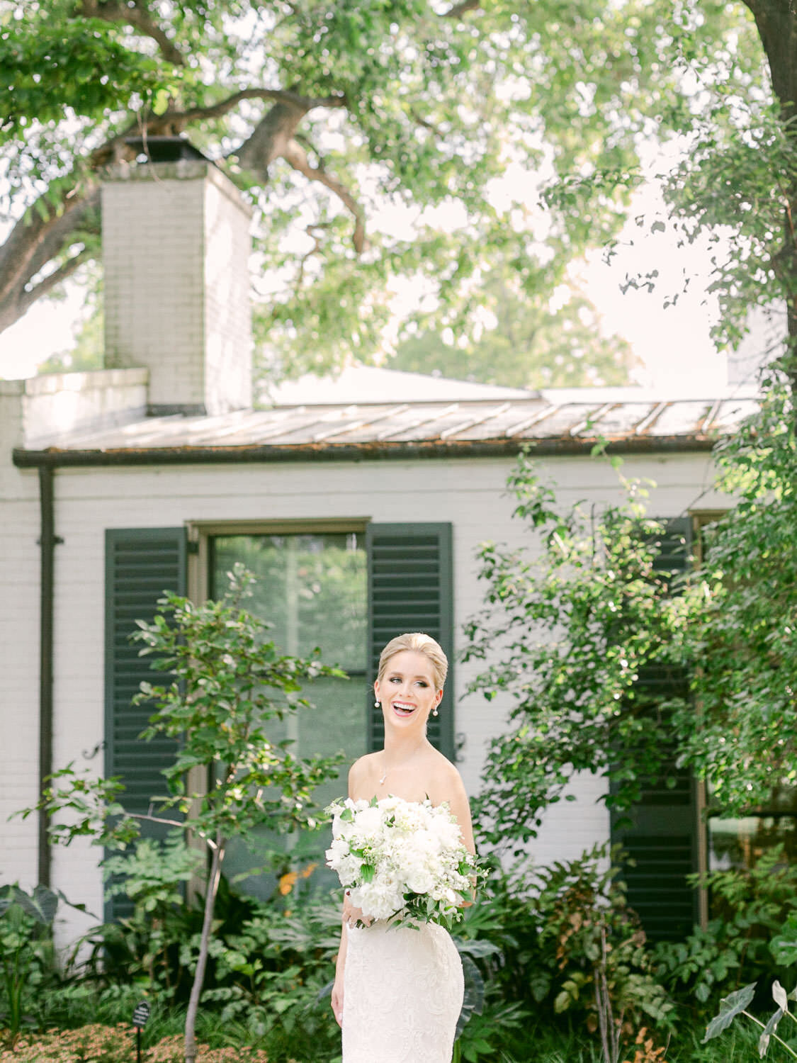 Bride holding white bouquet laughing in front of building with greenery at Dallas Arboretum Wedding